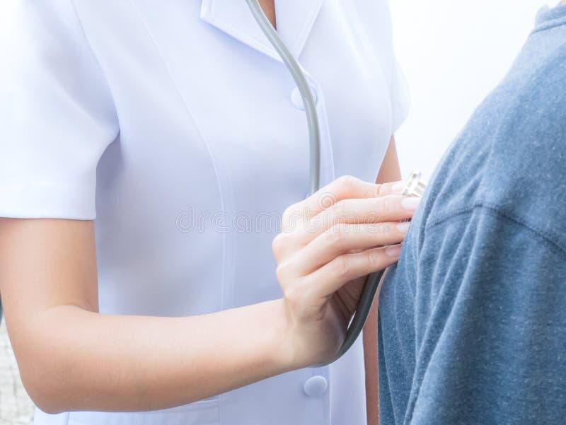 Krankenschwester überprüft Geduldsimpuls auf medizinischer Kontrolle lizenzfreie stockfotografie