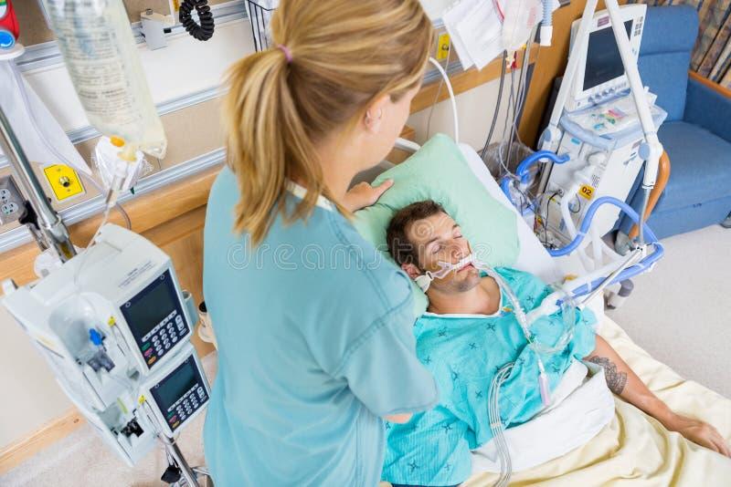 Krankenschwester Adjusting Young Patients Kissen im Krankenhaus stockfotos