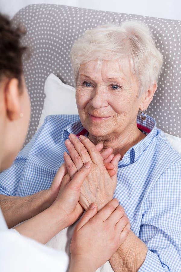 Krankenschwester, die ältere Frau tröstet stockbild