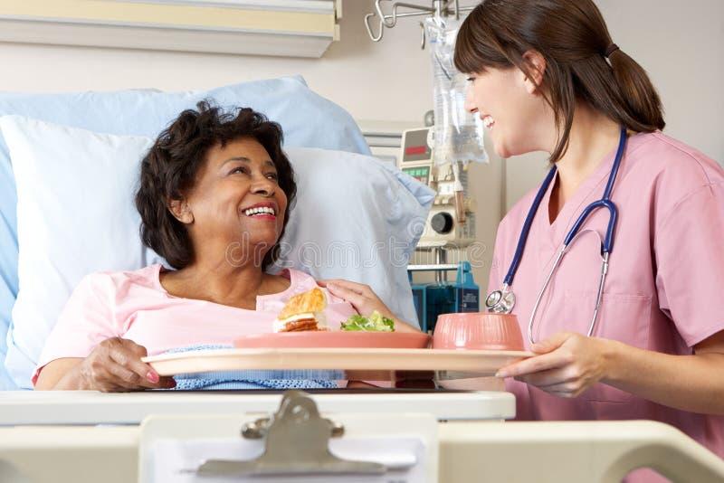 Krankenschwester, die ältere weibliche geduldige Mahlzeit im Krankenhaus-Bett dient lizenzfreie stockfotografie