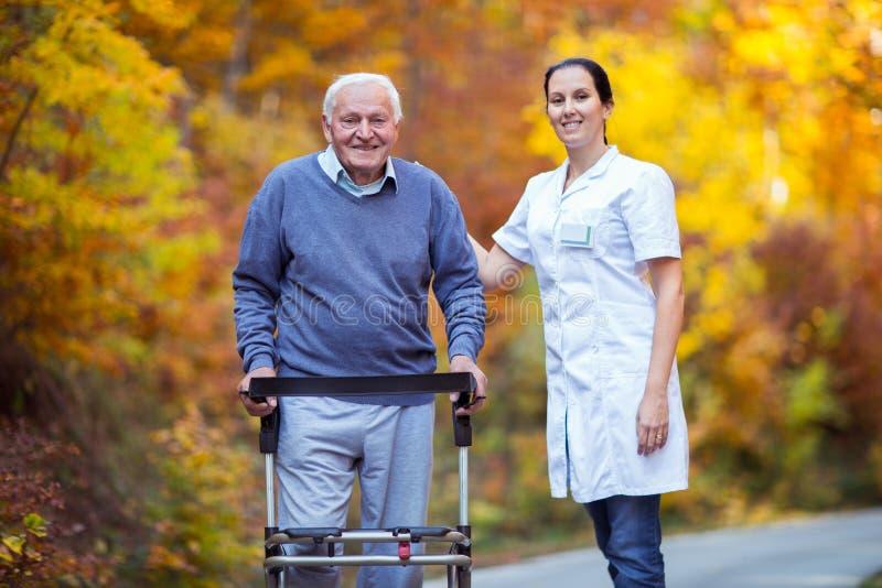 Krankenschwester, die älterem älterem Mann hilft stockfotos