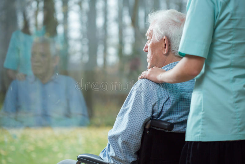 Krankenschwester, die älteren Mann unterstützt stockfotografie