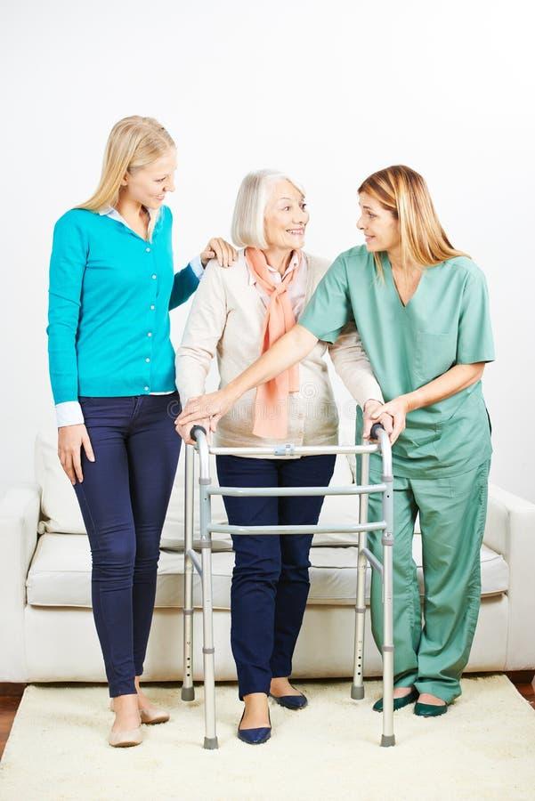 Krankenschwester, die älterer Frau mit Wanderer hilft stockfotografie