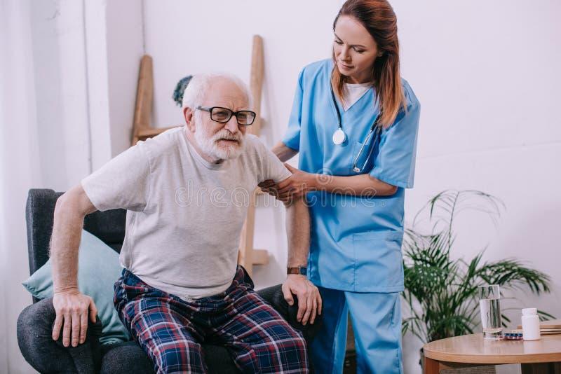 Krankenschwester, die altem Mann hilft, oben zu stehen lizenzfreies stockfoto