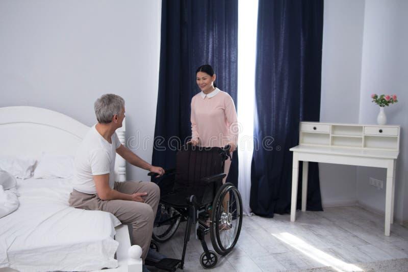 Krankenschwester, die arbeitsunfähigen Mann unterstützt stockfotos