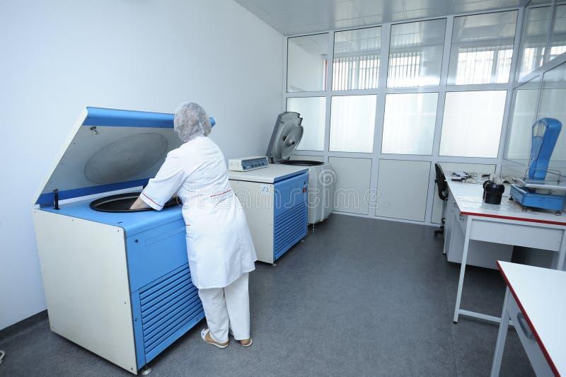 Krankenschwester, die Behälter mit Blut in eine Zentrifuge legt stockfotografie