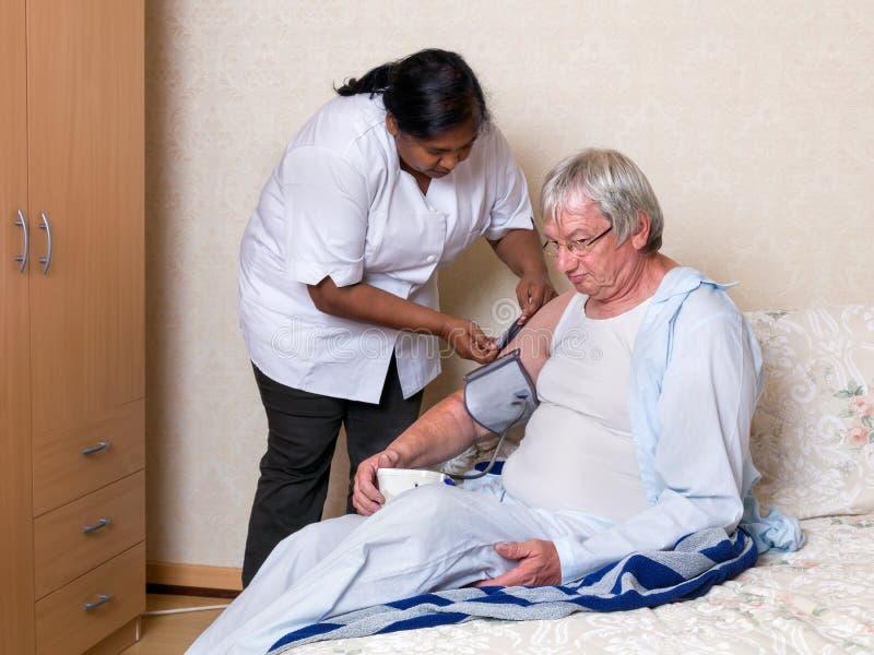 Krankenschwester, die Blutdruck überprüft stockbild