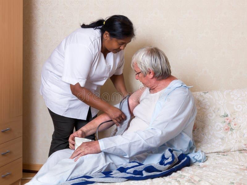 Krankenschwester, die Blutdruck des älteren Mannes nimmt stockbild