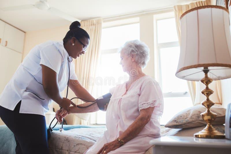 Krankenschwester, die Blutdruck des weiblichen Patienten überprüft stockfoto