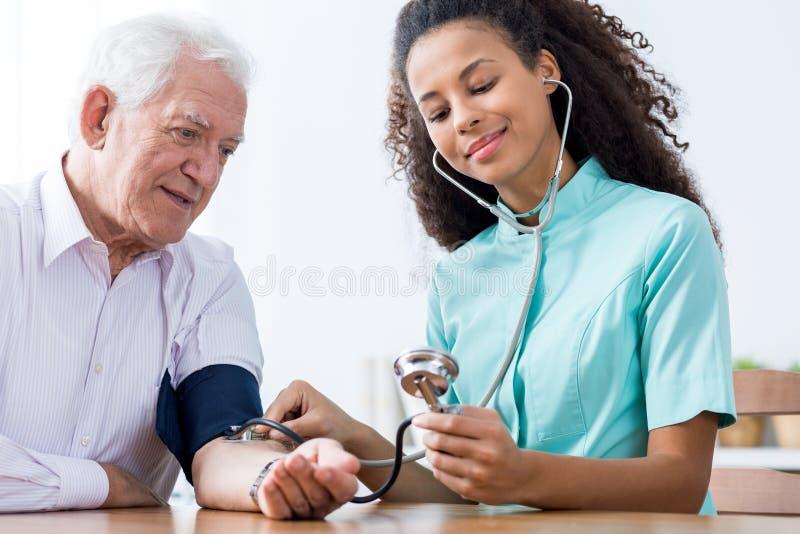 Krankenschwester, die Blutdruck nimmt stockbilder