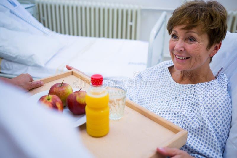 Krankenschwester, die dem Patienten ein Frühstück dient stockfotos