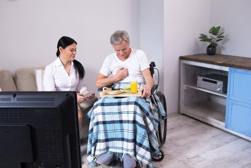 Krankenschwester, die dem Patienten im Rollstuhl Lebensmittel holt lizenzfreie stockfotos