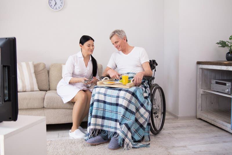Krankenschwester, die dem Patienten im Rollstuhl Lebensmittel holt lizenzfreie stockbilder