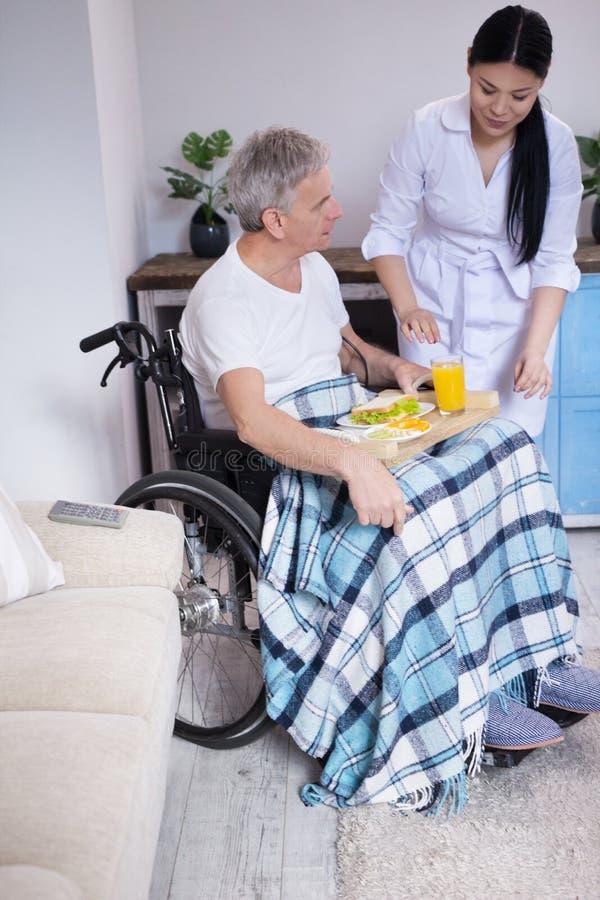 Krankenschwester, die dem Patienten im Rollstuhl Lebensmittel holt stockfotos