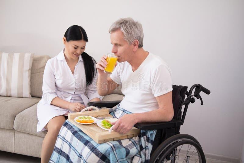 Krankenschwester, die dem Patienten im Rollstuhl Lebensmittel holt stockfoto