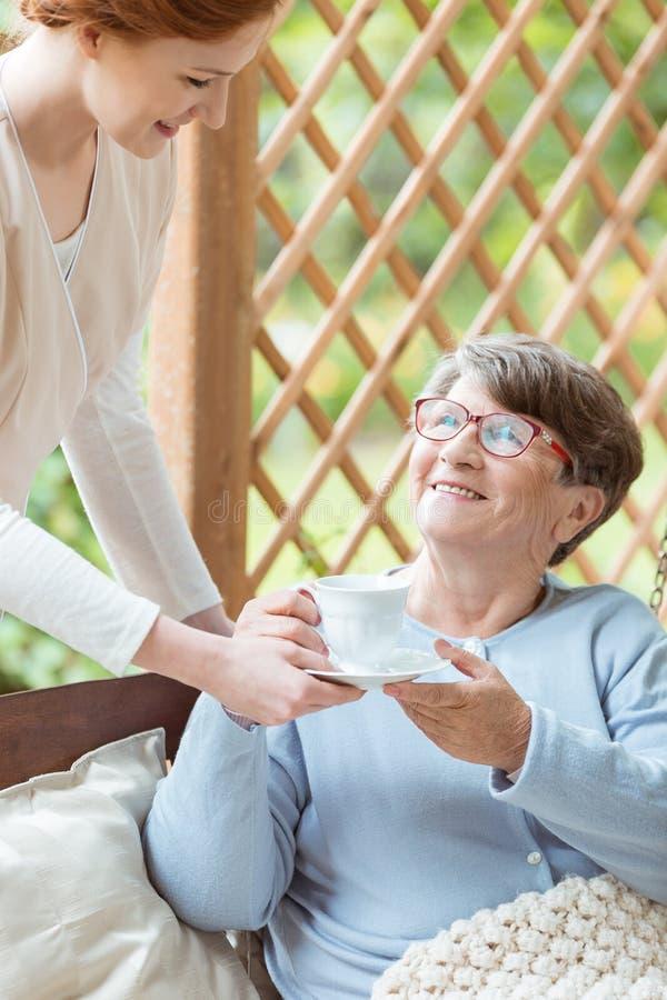 Krankenschwester, die dem Senior Tee holt lizenzfreie stockfotografie