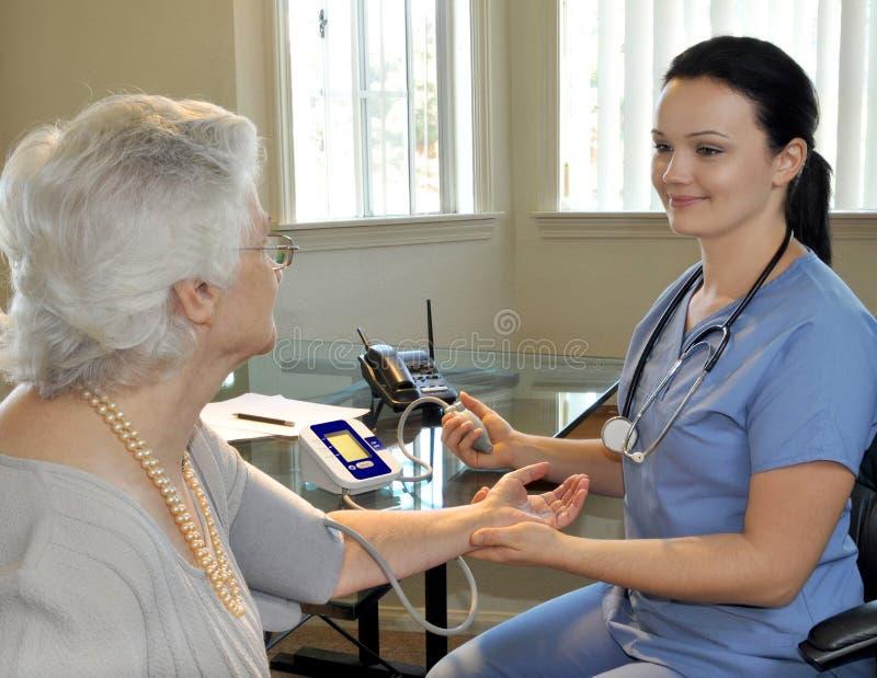 Krankenschwester, die den Blutdruck des Patienten misst stockbild