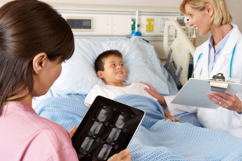Krankenschwester, die Digital-Tablette verwendet, während, Patienten besuchend stockfotografie