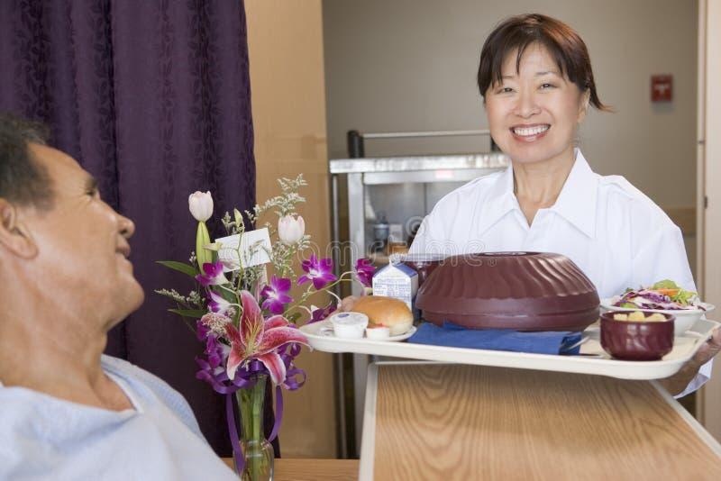 Krankenschwester, die einem Patienten eine Mahlzeit in seinem Bett dient lizenzfreies stockfoto