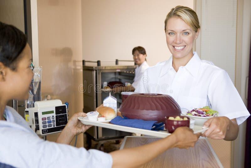 Krankenschwester, die einem Patienten eine Mahlzeit in seinem Bett dient stockbild