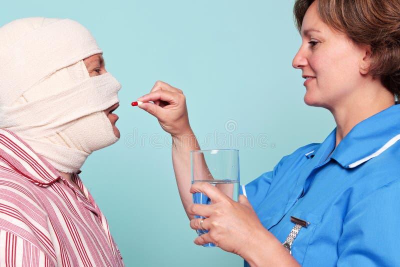 Krankenschwester, die einem Patienten etwas Medizin gibt stockfoto