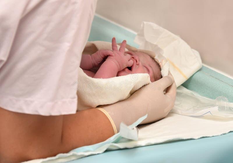 Krankenschwester, die für neugeborenes nach Geburt sich interessiert stockfotografie