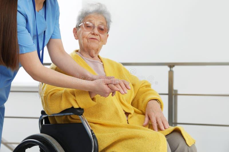 Krankenschwester, die Hand der älteren Frau im Rollstuhl am Krankenhaus massiert stockfoto