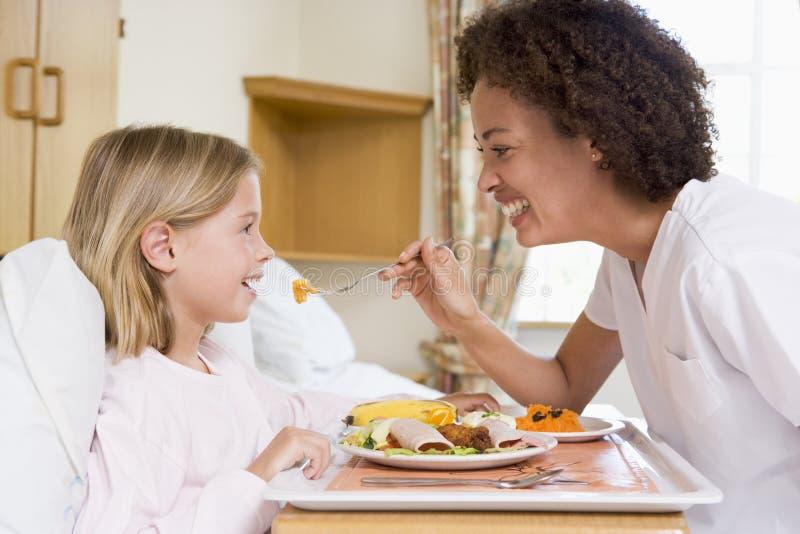 Krankenschwester, die junges Mädchen speist lizenzfreies stockfoto