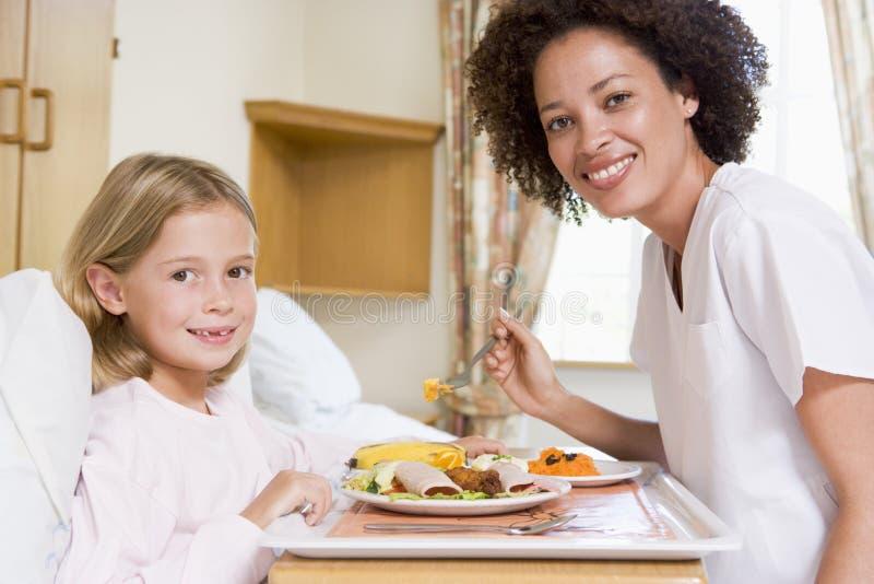 Krankenschwester, die junges Mädchen speist stockfotos