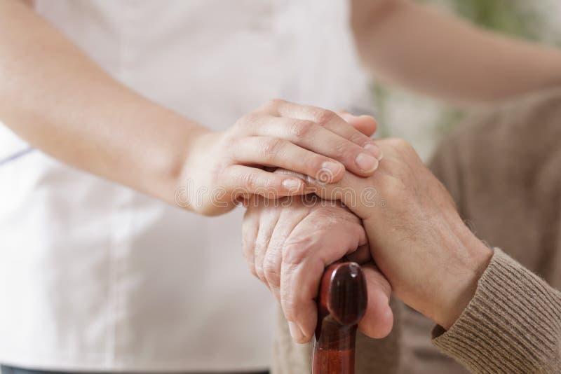 Krankenschwester, die kranken älteren Mann unterstützt lizenzfreies stockbild
