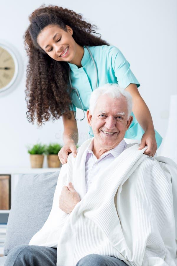 Krankenschwester, die kranken alten Mann stützt lizenzfreie stockbilder