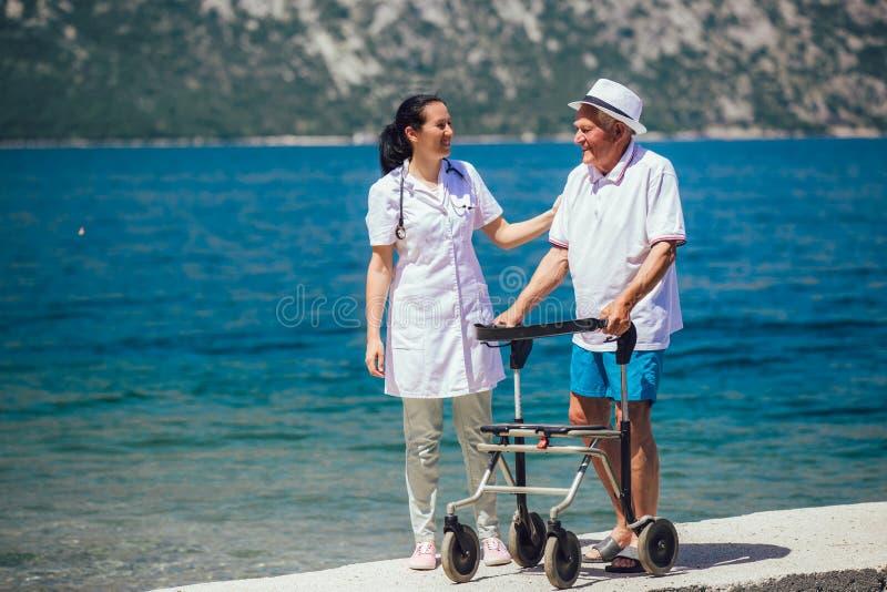 Krankenschwester, die ?lterem ?lterem Mann hilft stockbilder