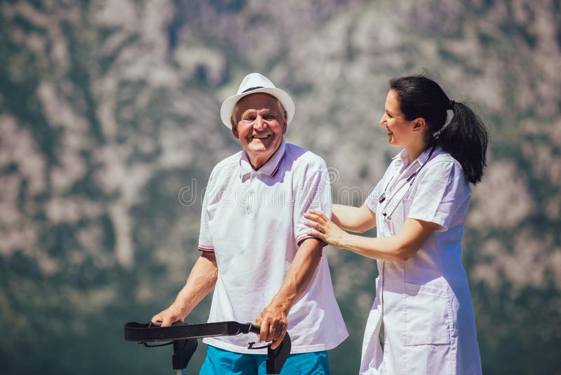 Krankenschwester, die ?lterem ?lterem Mann hilft lizenzfreie stockfotografie