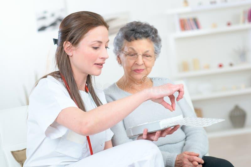 Krankenschwester, die Medikation mit älterer Frau bespricht lizenzfreie stockbilder
