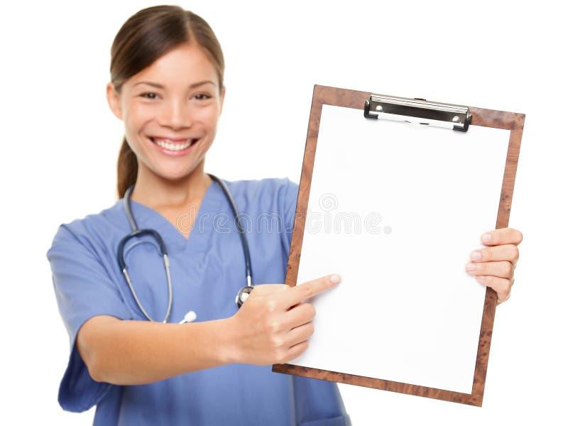Krankenschwester, die medizinischen Zeichenklemmbrett-Kopienraum zeigt lizenzfreie stockbilder