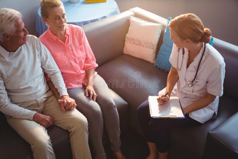 Krankenschwester, die mit älteren Paaren spricht lizenzfreies stockfoto