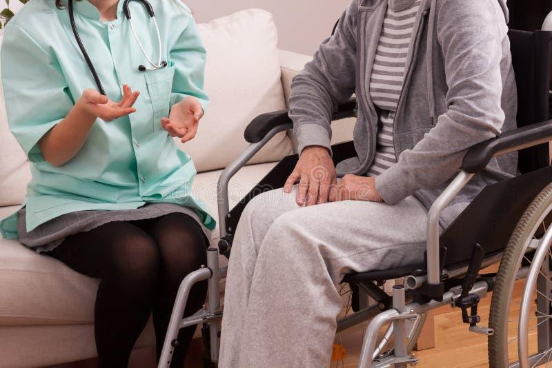 Krankenschwester, die mit behindertem Patienten spricht lizenzfreie stockfotografie