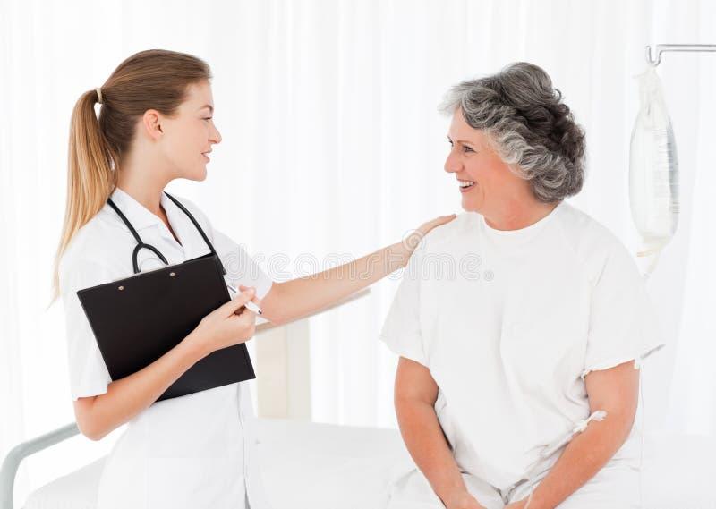 Krankenschwester, die mit ihrem Patienten spricht stockfotos