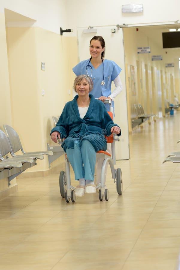 Krankenschwester, die Patienten im Rollstuhl drückt stockfotografie