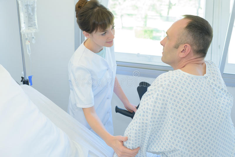 Krankenschwester, die Patientenhand auf Krankenhausbett hält stockfoto