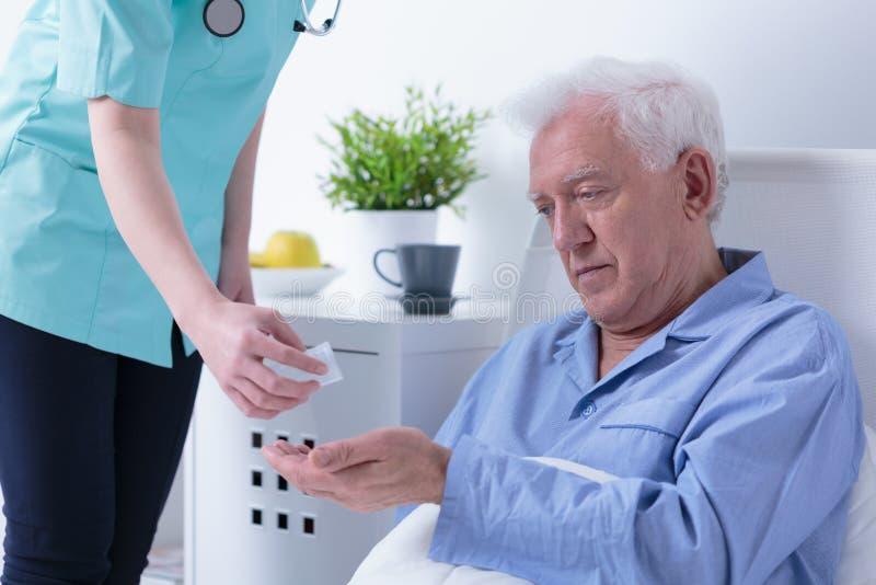 Krankenschwester, die Pillen gibt lizenzfreie stockfotos