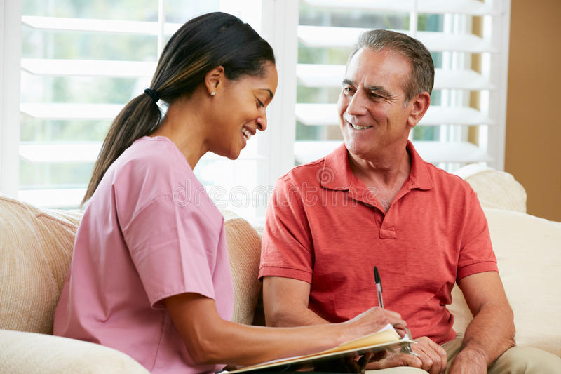 Krankenschwester, die Sätze mit älterem männlichem Patienten behandelt stockbild