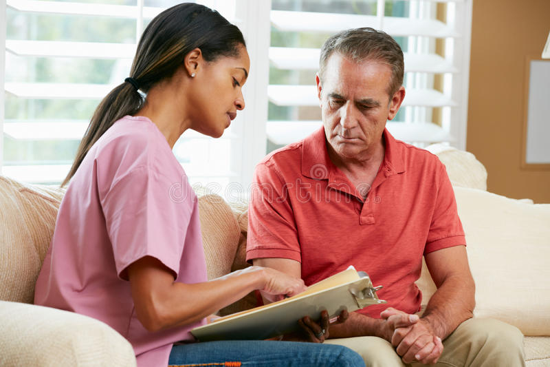 Krankenschwester, die Sätze mit älterem männlichem Patienten behandelt stockbilder
