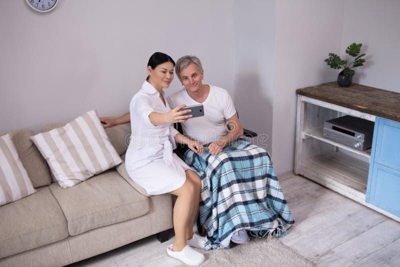 Krankenschwester, die selfie mit älterem Patienten nimmt lizenzfreie stockbilder
