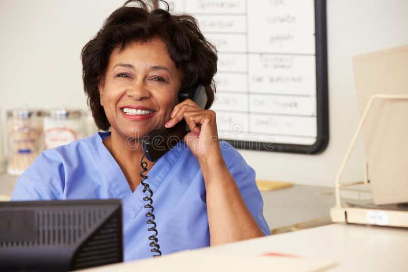 Krankenschwester, die Telefon-Aufruf an der Krankenschwester-Station macht stockfoto