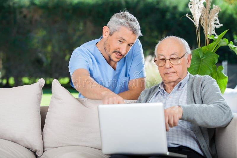 Krankenschwester-Explaining Something On-Laptop zum älteren Mann stockbild