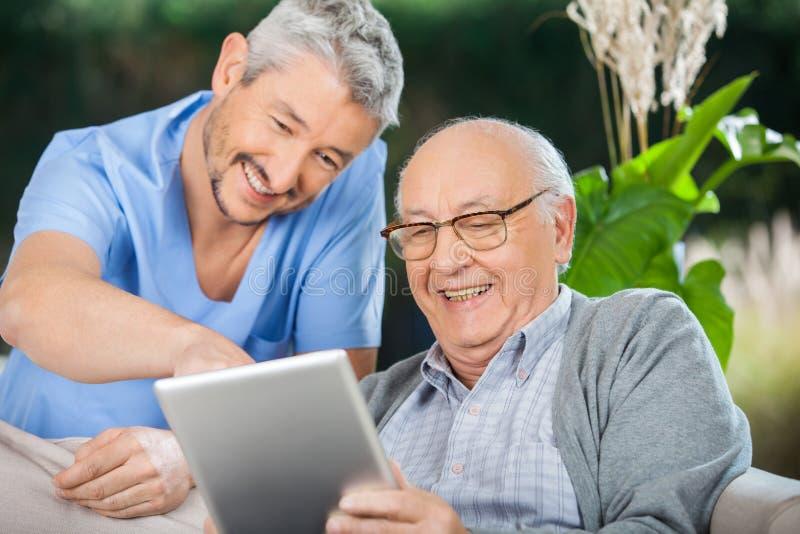Krankenschwester genießendes And Senior Man bei der Anwendung des Tablets stockfotografie