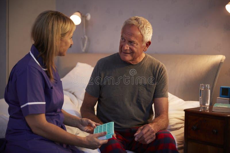 Krankenschwester Helping Senior Man, zum der Medikation auf Hausbesuch zu organisieren lizenzfreie stockfotos