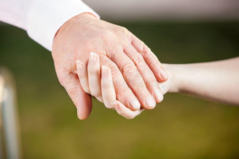 Krankenschwester Holding Senior Mans Hand lizenzfreie stockbilder