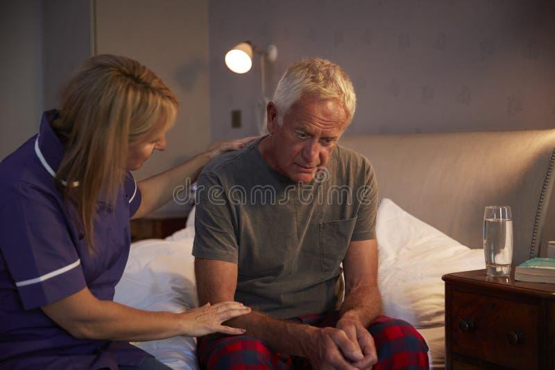 Krankenschwester Making Home Visit zum älteren Mann, der mit Krise leidet stockbild